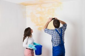 New homeowner and a painter look at a construction defect